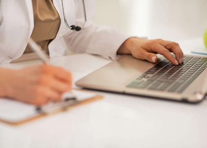 Medical professional sitting at a desk in front of a laptop and a paper chart