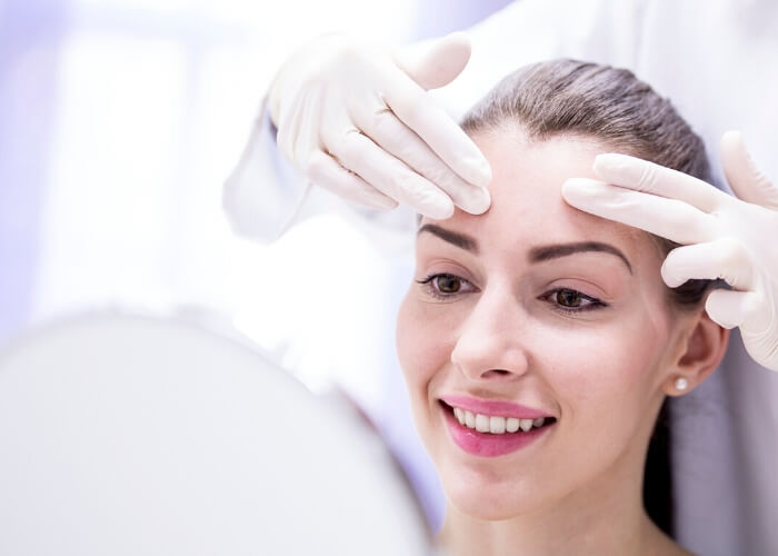 Smiling young woman looking in a mirror while a doctor with gloved hands examines her forehead