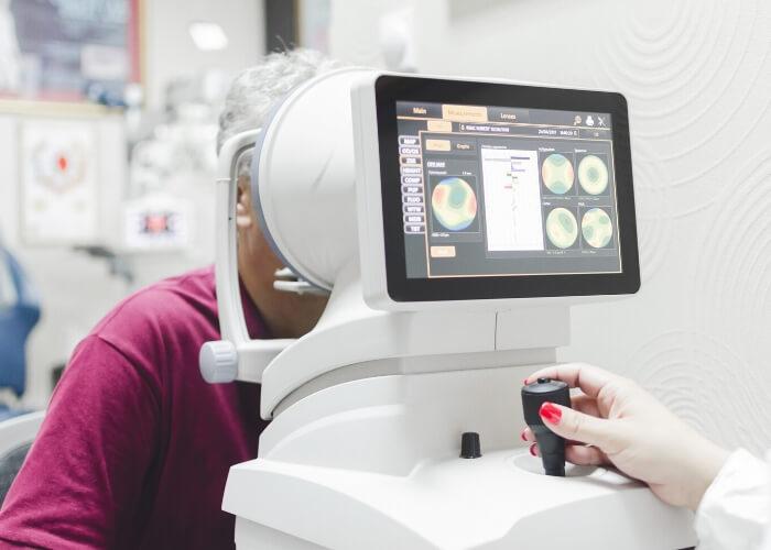 Elderly female patient undergoing an exam with an optical machine