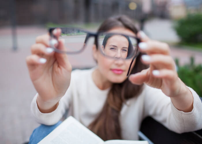 Blurry photo of a woman holding a pair of glasses toward the camera, with only her face seen through the lenses in focus